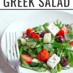 This Greek Salad Recipe features, tomatoes, olives, cucumber, feta cheese, fresh herbs, arugula, and a simple dressing prepared from lemon juice and olive oil!