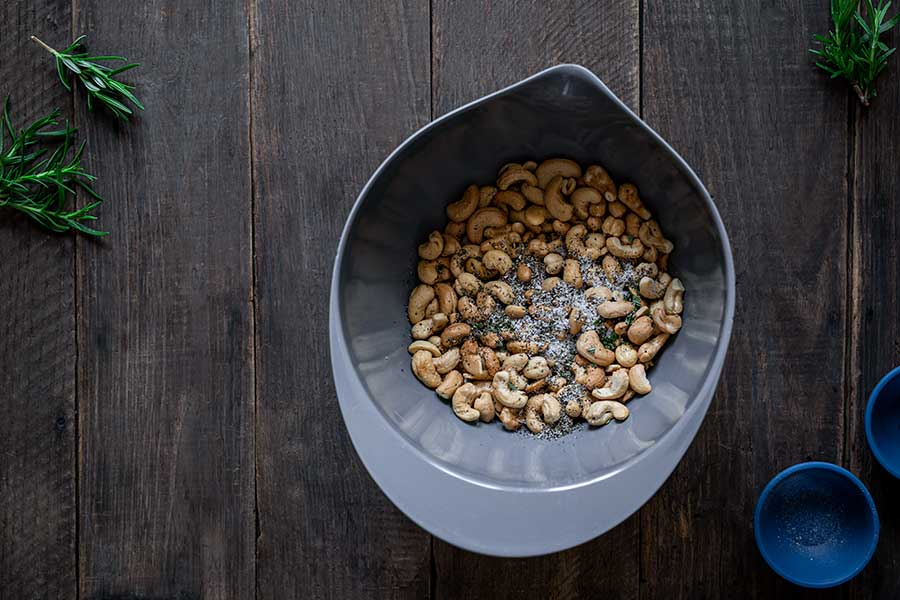 Roasted cashews in a grey bowl with salt, pepper, and rosemary on top prior to mixing