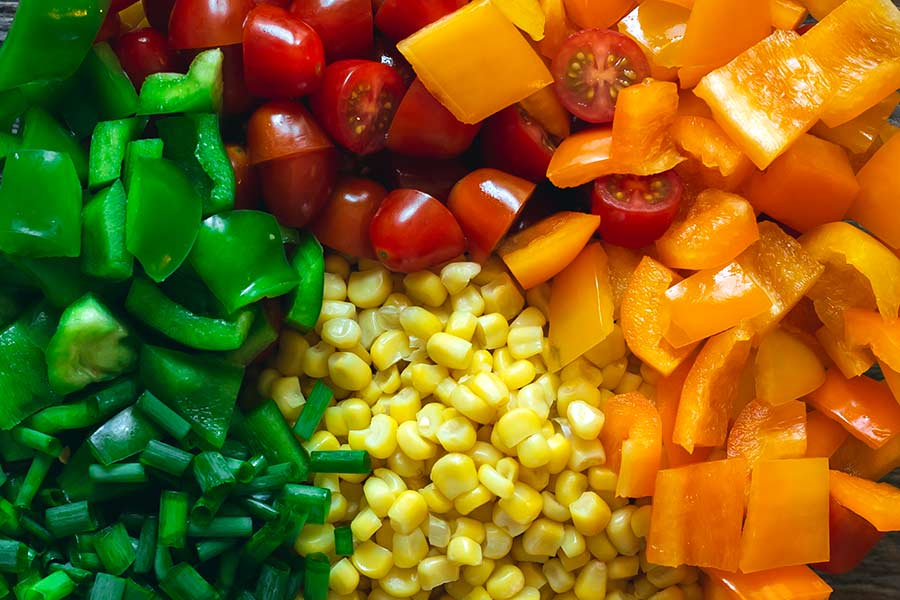 Closeup of ingredients, including bell peppers, tomatoes, and corn
