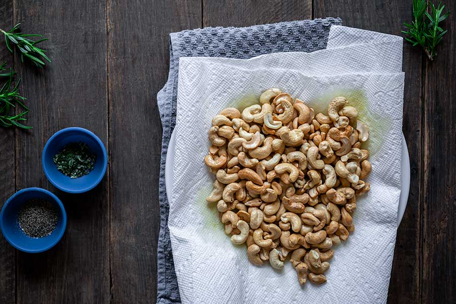 Toasted cashews draining on a paper towel-lined plate to remove oil