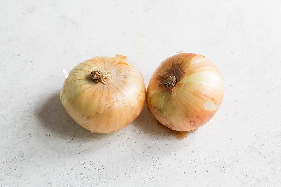 two vidalia onions on a white surface