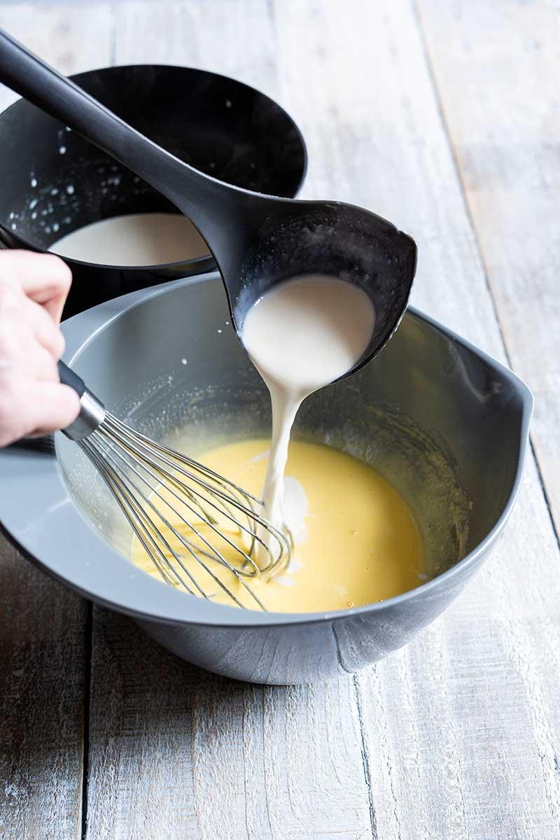 Tempering hot cream into yolk sugar mixture