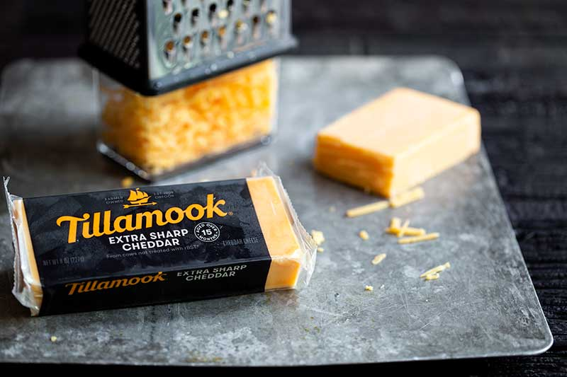 Tillamook extra sharp cheddar in it's packaging next to a block of cheddar and a box grater filled with cheese.