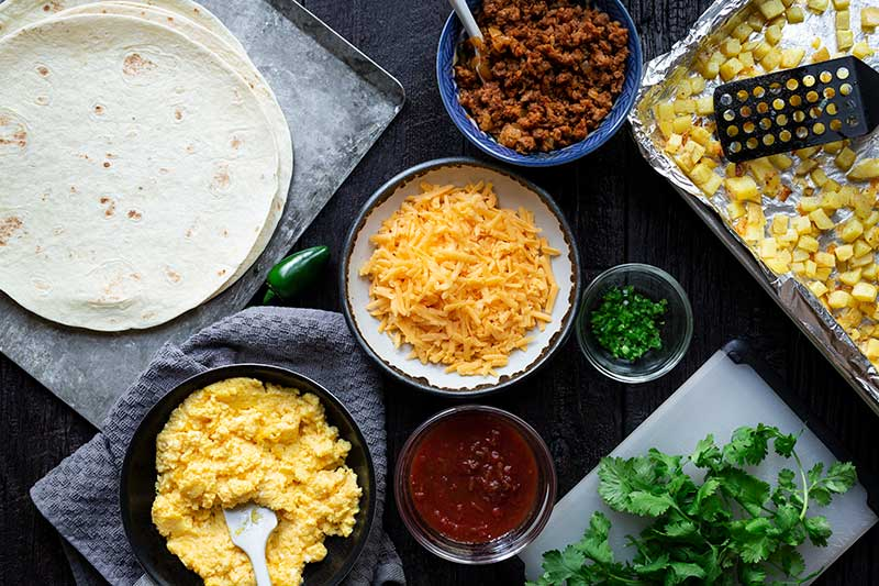 Overhead shot of ingredients laid out for easy breakfast burrito, including cooked chorizo, tortilla craps, cheese, cooked eggs, and salsa.