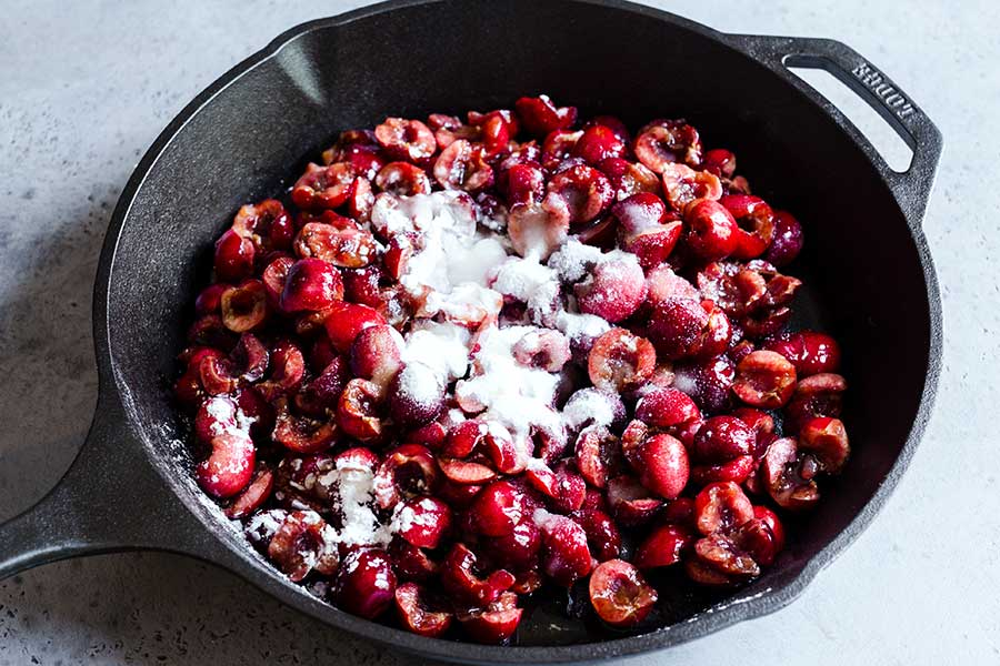 Uncooked cherries in a cast iron skilled with dry ingredients