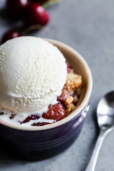 Cherry crisp in a small bowl topped with a scoop of vanilla ice cream