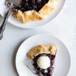 Overhead shot of full cherry galette and a single slice topped with ice cream