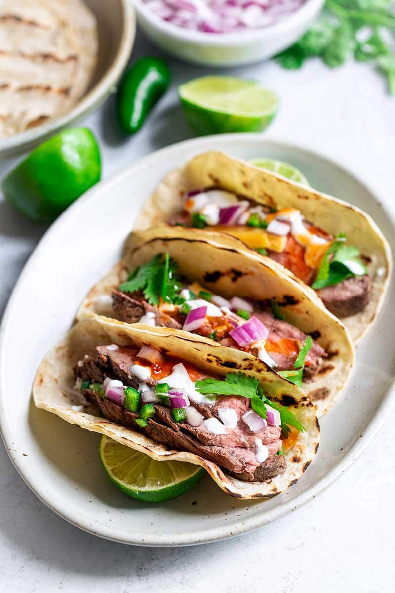 Three grilled steak tacos on an oval plate, surrounded by recipe ingredients.