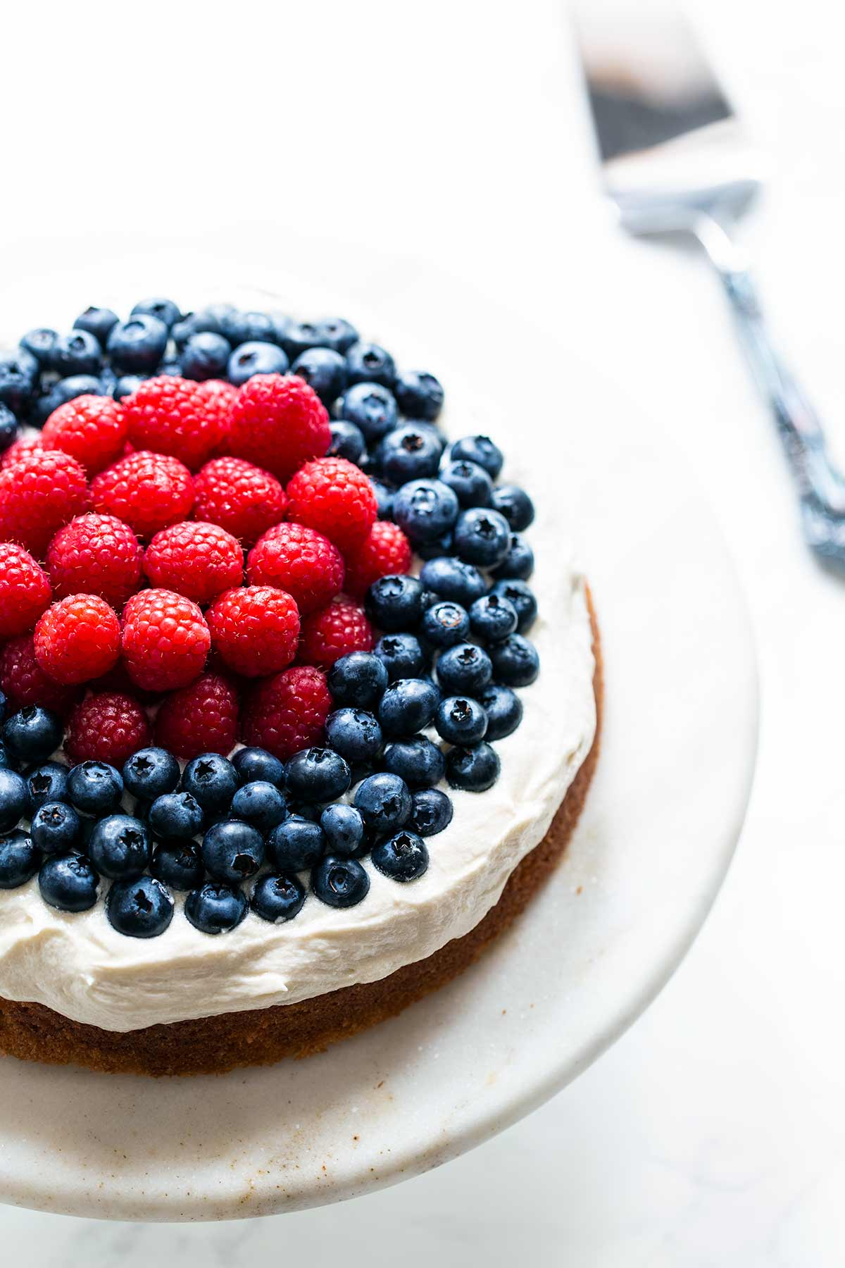 Bright photo of a white cake topped with a thick layer of cream cheese frosting, topped with raspberries in the center and blueberries toward the edge.
