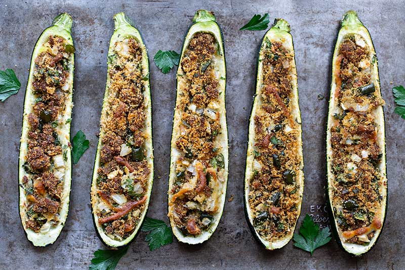 Finished stuffed zucchini on a sheet pan surrounded by fresh parsley