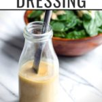 "Dressing recipe in a jar with salad in the background, and text overlay reading ""Easy Tahini Dressing"""