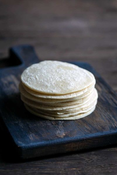 stack of homemade corn tortillas on a cutting board