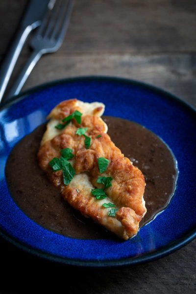 A photo of pan-seared chicken breast topped with a pan sauce recipe and fresh chopped parsley