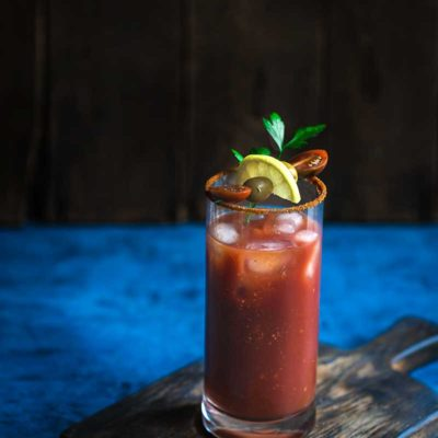 Old Bay Bloody Mary Recipe topped with garnishes on a blue backdrop