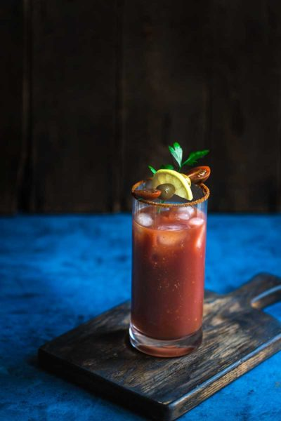 Old Bay Bloody Mary topped with garnishes on a blue backdrop