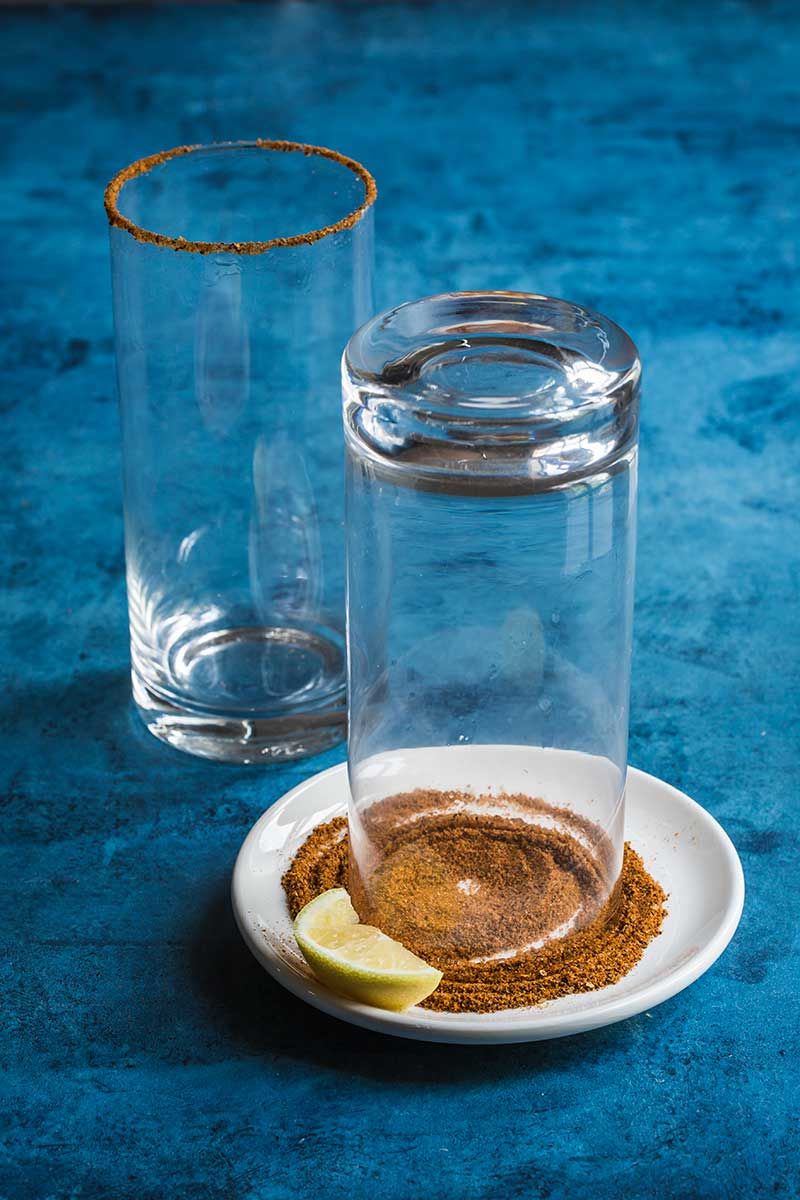 A highball glass turned over on a small plate covered with Old Bay Seasoning for the rim