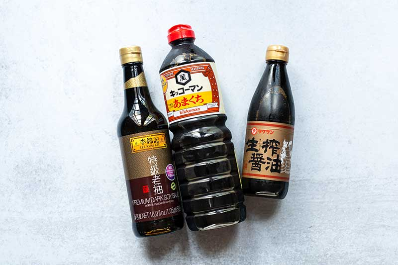 Three bottles of soy sauce laid out next to one another