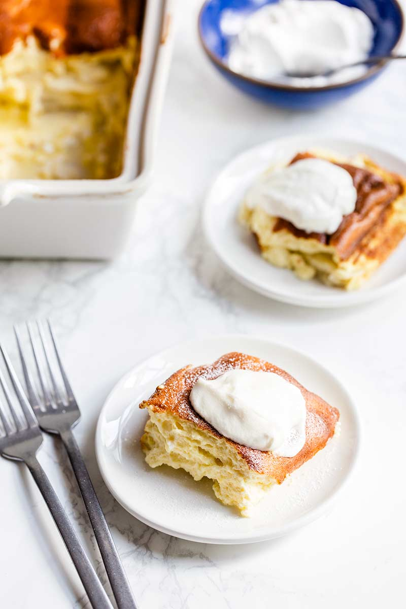 close up of blintz souffle on a plate topped with sour cream and sugar
