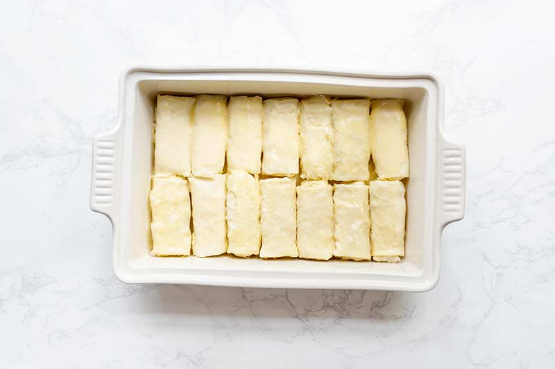 14 cheese blintzes packed into a single layer in a casserole dish
