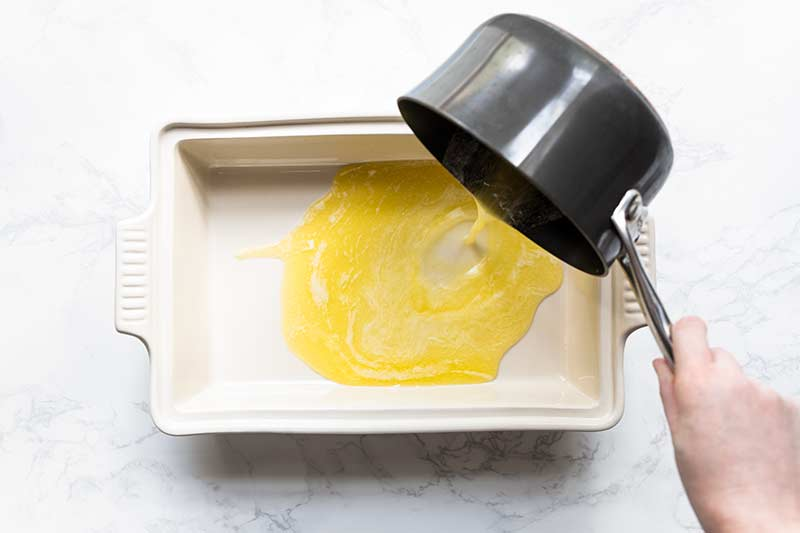 pouring melted butter from a saucepan into a casserole dish