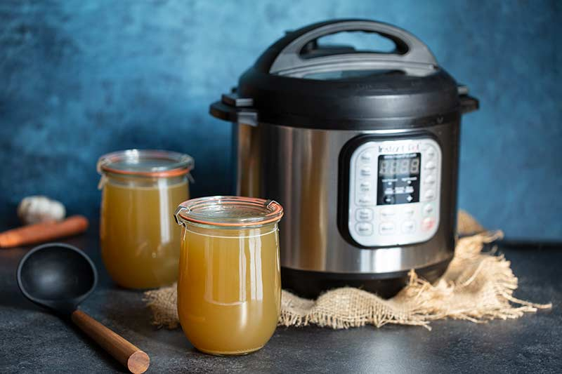 Pressure cooker chicken stock in mason jars in front of an Instant Pot