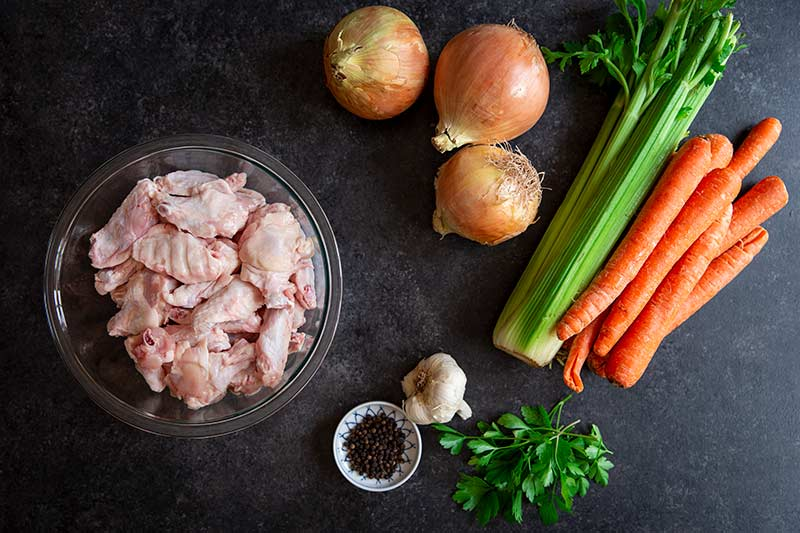 Ingredients on black background for making a chicken stock recipe