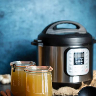 Chicken stock in two large mason jars in front of an Instant Pot pressure cooker