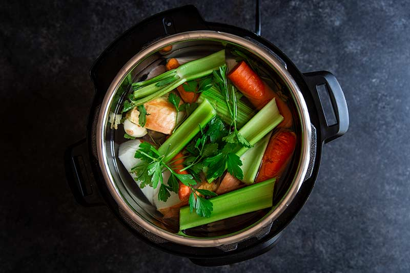 celery, onion, carrots and water in an Instant Pot