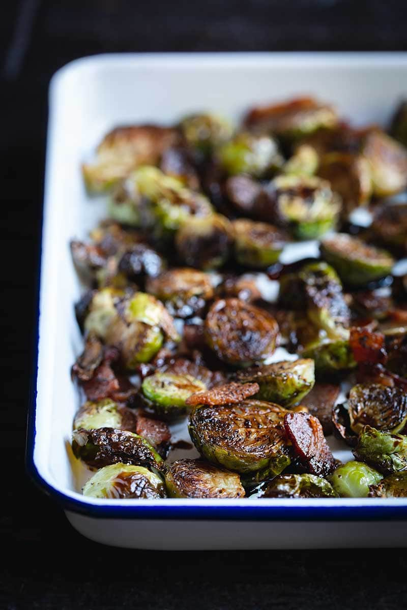Roasted balsamic bacon Brussels Sprouts in a white serving pan.