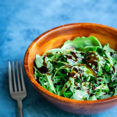 Balsamic reduction recipe drizzled over arugula with fork