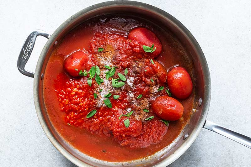 Unmixed ingredients for tomato sauce in skillet