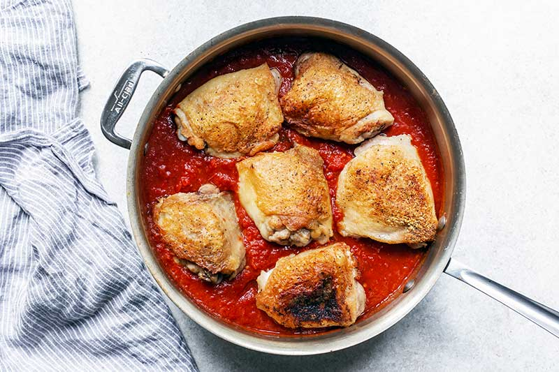 chicken placed back into the skillet, nested in the sauce