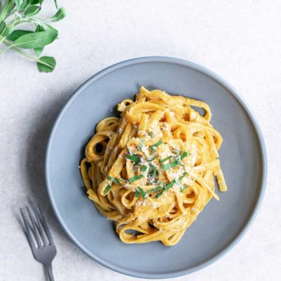 Creamy pumpkin pasta recipe on a blue plate, topped with sage and parmesan cheese