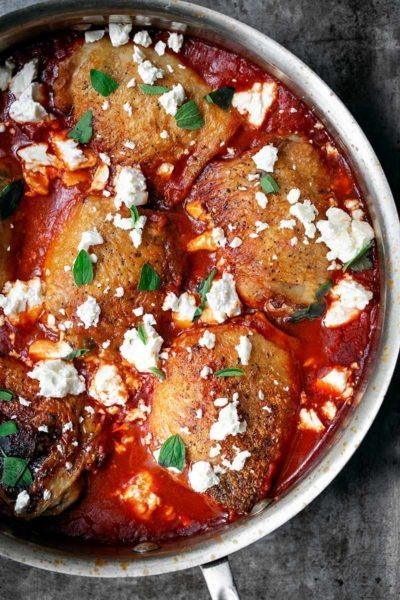 A closeup photo of crispy chicken thighs with spiced tomato sauce in a skillet