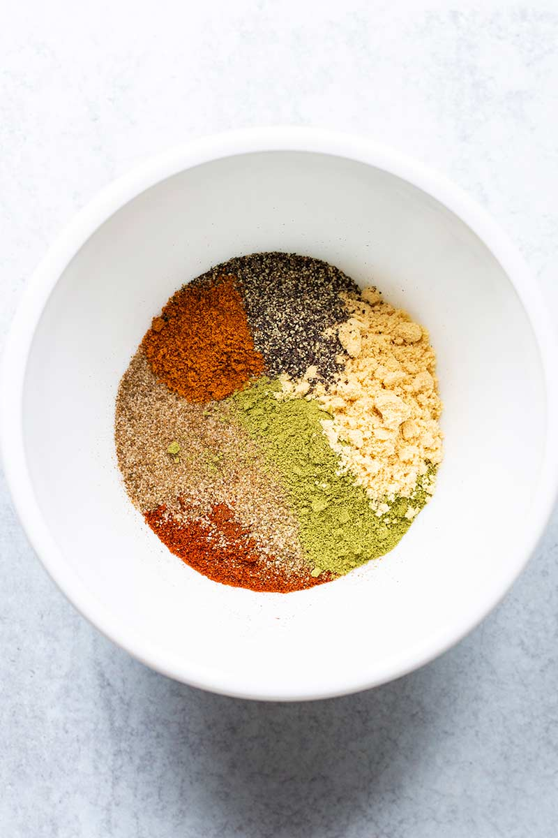 Closeup of a bowl with unblended spices for homemade old bay seasoning