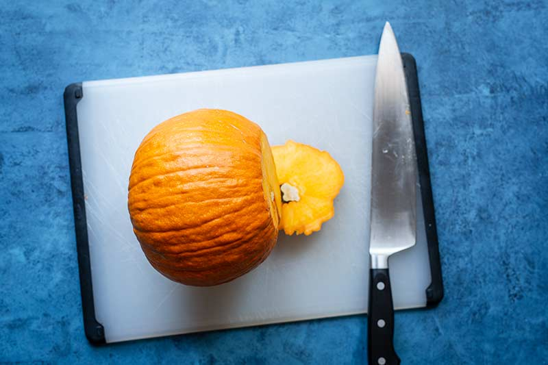 A pumpkin laying on its side on a cutting board with the stem removed.