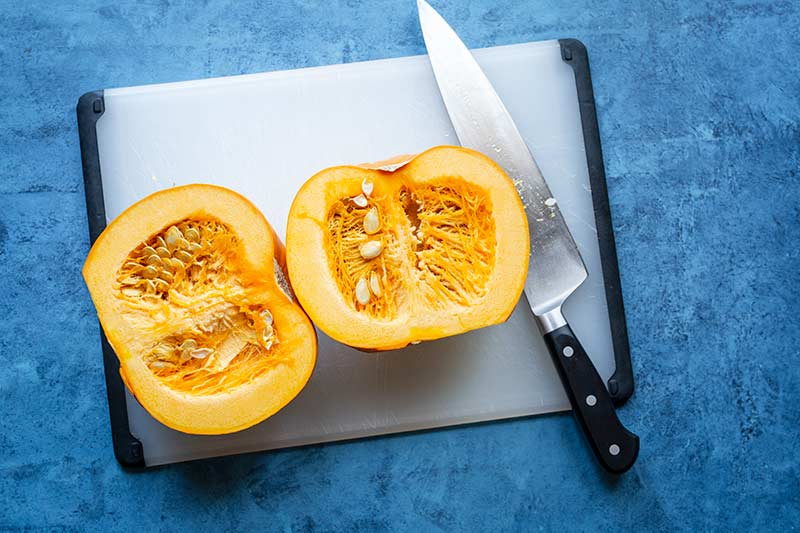 Two pumpkin halves laying flesh side up on cutting board