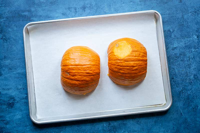 Two seeded pumpkin halves lying flesh side down on a sheet pan lined with parchment paper