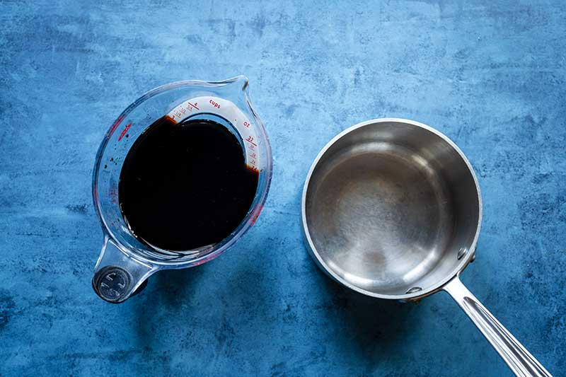 3 cups of balsamic vinegar in liquid measuring cup next to saucepan