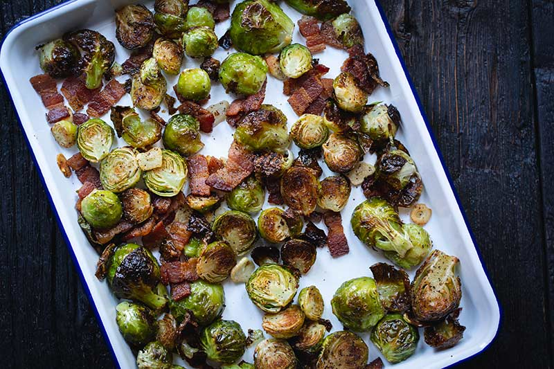 fully roasted brussels sprouts with bacon just out of the oven, still on the sheet pan.