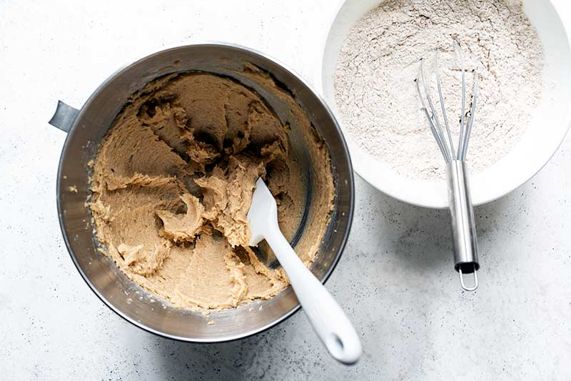 Butter and sugar creamed in a mixing bowl next to dry ingredients whisked together in a separate bowl