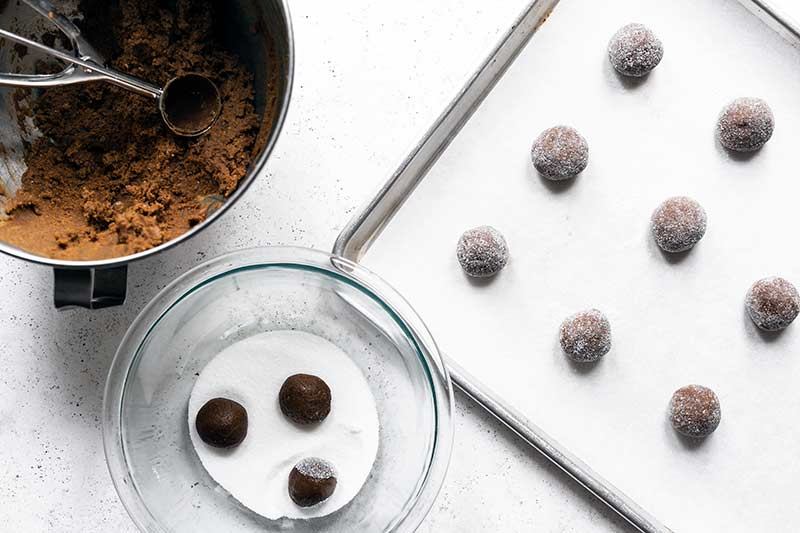 A mixer with cookie dough, a bowl of sugar for tossing raw cookies, and a sheet pan with unbaked molasses cookies