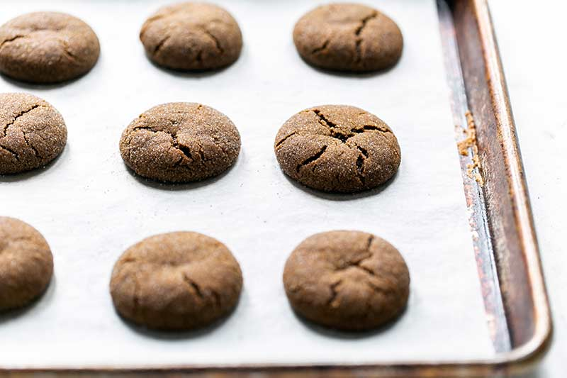 Soft, Chewy Molasses cookies on a sheet pan lined with parchment