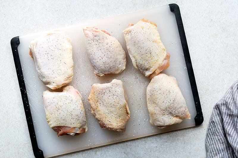 Raw, bone-in skin on chicken thighs on a cutting board