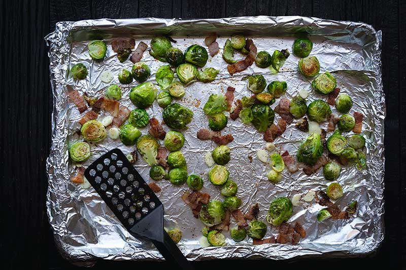 A foil-lined sheet pan topped with partially roasted brussels sprouts, bacon, olive oil, sliced garlic, salt and pepper.