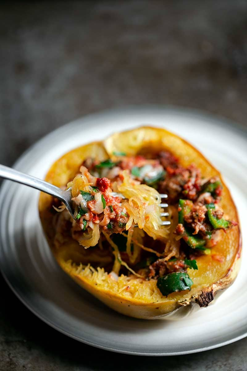 A Baked Spaghetti Squash Boat on a plate with a fork scooping up some of the filling