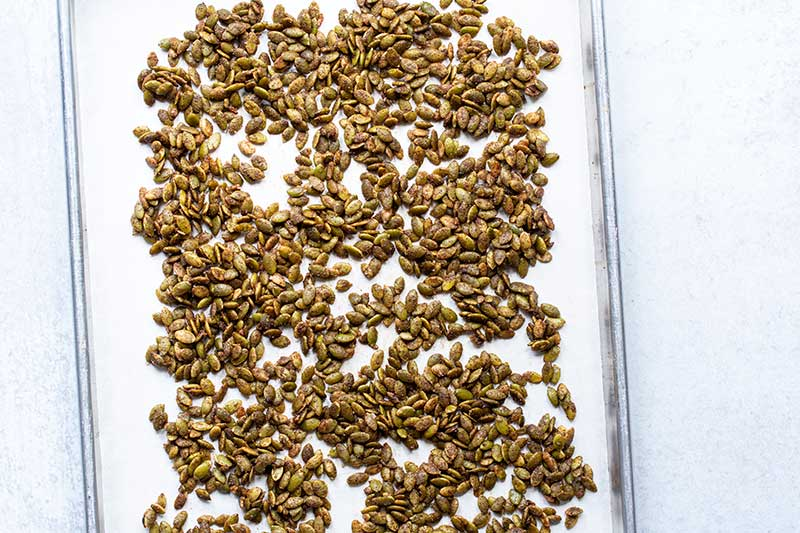 A parchment-lined sheet pan topped with raw pumpkin seeds tossed in remaining ingredients