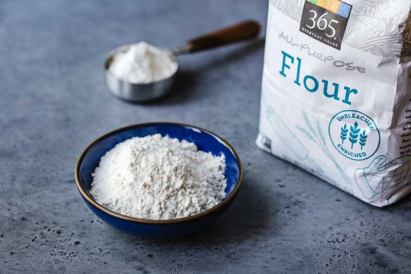 all-purpose flour in a bowl next to the package