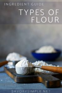 Different types of flour displayed in bowls and measuring cups