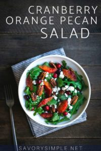 Cranberry orange salad recipe in a salad bowl with a fork and napkin